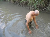 Old man washing himself in the water next to his field Stock Photo