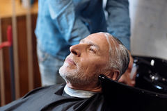 Old man during washing his hair in barber shop Royalty Free Stock Photos