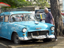 Old man washing his vintage car in Havana. Stock Image