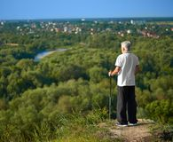 Old man watching the city panorame keeping tracking sticks. Old man watching beatiful city panorame keeping tracking sticks. Standing on green grassy hill stock photography