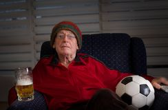 Old man watching football match. Old man sitting in armchair holding soccer ball and mug of beer and looking at tv, feeling scared and disappointed stock images
