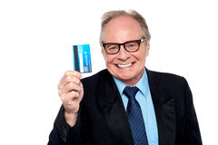 Old man wearing eyeglasses holding up a cash card Stock Photos