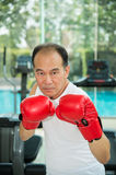 Old man wearing red boxing gloves exercising in fitness or gym, Health concept. Old man wearing red boxing gloves exercising in fitness or gym, look to camera Stock Photo