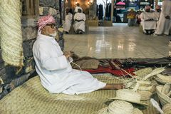 The old man is weaving straw hats to meet guests in the pavilio. DUBAI, UAE - DECEMBER 4, 2017: The old man is weaving straw hats to meet guests in the pavilion royalty free stock photography