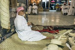 The old man is weaving straw hats to meet guests in the pavilio. DUBAI, UAE - DECEMBER 4, 2017: The old man is weaving straw hats to meet guests in the pavilion royalty free stock photos