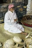 The old man is weaving straw hats to meet guests in the pavilio. DUBAI, UAE - DECEMBER 4, 2017: The old man is weaving straw hats to meet guests in the pavilion royalty free stock image