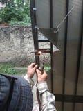 Old Man Welding a Corrosive Black Iron Handle of Gate. Photo Old Man Welding a Corrosive Black Iron Handle of Gate stock image