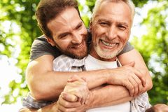 The old man on a wheelchair and his son are walking in the park. A man hugs his elderly father. The old men on a wheelchair and his son are walking in the park royalty free stock photos