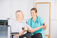 Old man in wheelchair lifting dumbbells Stock Photo