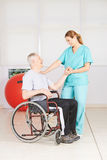 Old man in wheelchair at physiotherapy Royalty Free Stock Images