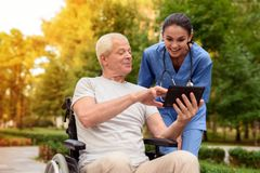 An old man in a wheelchair proudly shows a happy nurse something in his tablet. Have something to be proud of. An old men in a wheelchair proudly demonstrates to Royalty Free Stock Images