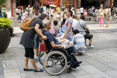 Old man in a wheelchair on qianmen street in Beijing Stock Photography