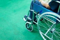 An old man in a wheelchair seats. stock photos