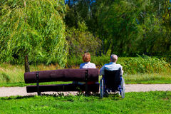 Old man on wheelchair and young woman on a bench. Old men on wheelchair and young women on a bench sitting in the park Royalty Free Stock Photo