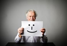 Old man in white is holding white paper with smile. Royalty Free Stock Photo