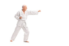 Old man in a white kimono practicing karate. Full length profile shot of an old man in a white kimono practicing karate isolated on white background Stock Photo