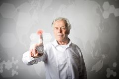 Old man in white pushing the button. Innovative technology conce. Old man in white is pushing the virtual hexagonal button. Innovative technology concept Royalty Free Stock Images