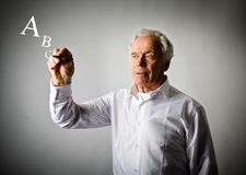 Old man is writing something. Letters. Alphabet. Old man in white is writing something. Old man in white and letters. Alphabet Stock Images