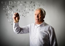 Old man is writing something. Letters. Old man in white is writing something. Old man in white and letters Royalty Free Stock Image