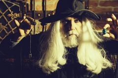 Old wizard pendant for hypnosis. Old man wizard with long gray hair beard in black costume and hat for Halloween holding blue gem stone and silver pendant for stock photo