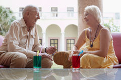 Old man and woman drinking in hotel's bar stock image