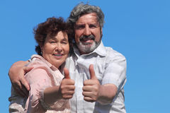 Old man and woman making thumbs up gesture stock image