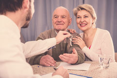 Old man and woman sign rent agreement Stock Photos