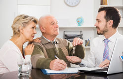 Old man and woman sign sale agreement Stock Image