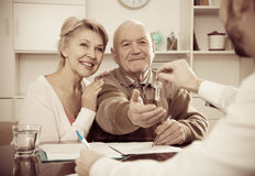 Old man and woman sign sale agreement Stock Images