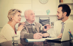 Old man and woman signing car purchase contract. Old men and and women signing car sale contract at office and hand over keys to manager royalty free stock images