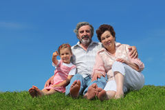 Old man and woman sitting with granddaughter. Barefooted old man and woman sitting on lawn with their granddaughter, girl pointing by finger Royalty Free Stock Photos