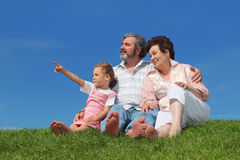 Old man and woman sitting with granddaughter. Barefooted old man and woman sitting on lawn with their granddaughter, girl pointing by finger at side Stock Images