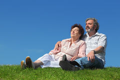 Old man and woman sitting on lawn Royalty Free Stock Image