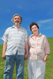 Old man and woman standing on summer lawn Stock Photos