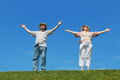 Old man and woman in straw hats standing on lawn Stock Photography