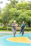Old man and woman to play basketball in the morning so happily. stock photography