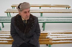 Old man wondering about life. Old man sitting on the bench in the park Royalty Free Stock Photo