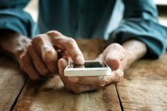 Old man working with digital smartphone, stock photo