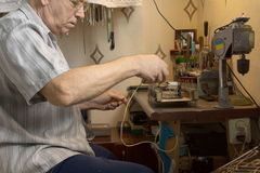 Old Man Working Electronic Device on Small Table Royalty Free Stock Photos