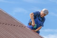 Old man working at heat on a roof of a house with electric screwdriver, wearing no safety devices, work clothing, blue overall, da. Ngerous job, elder people at royalty free stock photo