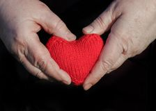 Old man with wrinkled hands with fingers knitted red heart Royalty Free Stock Photo