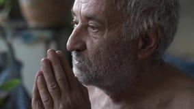 Old poor man praying at home. Old man with wrinkles praying stock video footage