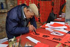 FOSHAN, CHINA - CIRCA JANUARY 2018: An old man writing blessing antithetical couples during the Spring Festival. royalty free stock photo