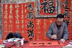 FOSHAN, CHINA - CIRCA FEBRUARY 2018: An old man writing blessing couplets at the occasion of Spring festival. The meaning of the c. An old man writing blessing stock image