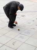 Old man writing chinese handwriting on the floor Royalty Free Stock Photo