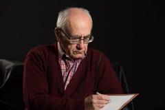 Old man writing Stock Image