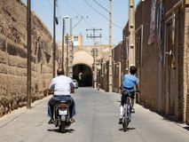 Old man and young boy, riding a motocycle scooter and a bicycle in the streets of the old Yazd, the main city of central Iran. Picture of two persons, a teenager stock photos