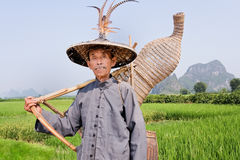 Old man of Zhuang minority in the fields of Yangshuo, China. YANGSHUO, CHINA – SEPT. 18, 2006. Old man of the Zhuang minority on Sept. 18, 2006. Guanxi Royalty Free Stock Images