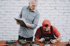 Old Manager Checking Motherboard near Worker royalty free stock photos
