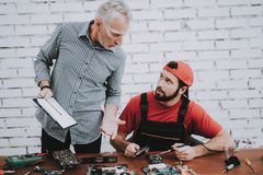Old Manager Checking Motherboard near Worker. royalty free stock image